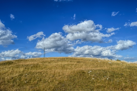 Mountain meadow and electricity transmission line under blue sky with some clouds photo