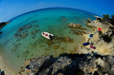 Rubber dinghy, anchored nearby small  lagoon, hidden among rocks, Sithonia, Greece, fisheye view from above photo