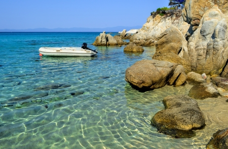 Rubber dinghy, anchored nearby small  lagoon, hidden among rocks, Sithonia, Greece  photo