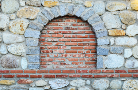 Stone wall with bricked up round window, suitable space for text