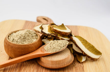 grinded: Close up view of a pile of sliced and minced dried porcini mushrooms in a wooden bowl and wooden teaspoon on a chopping board