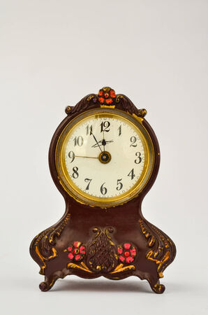 Old-fashioned musical alarm clock over white, showing five to twelve as a deadline and nine o