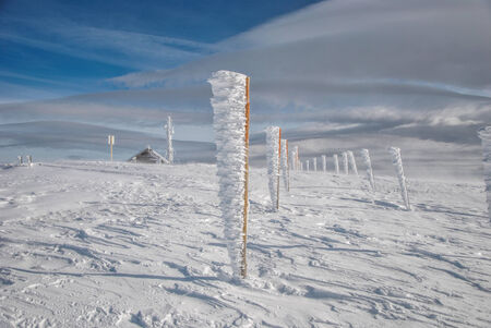 Frozen iron pillars, completely covered by snow and icicles and mountain winter landscape under blue sky with some high clouds photo