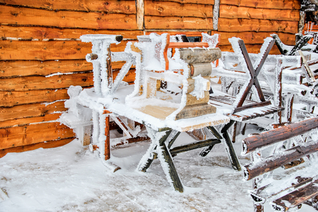 Frozen benches and tables lined on podium of rustic restaurant, waiting for favorable weather conditions photo