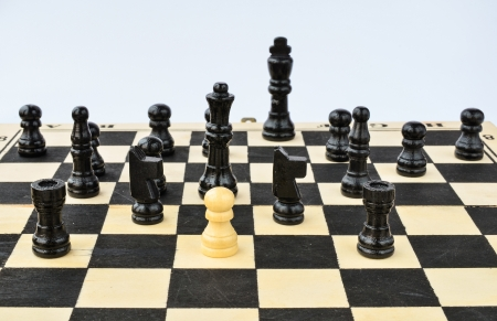 White pawn standing alone, surrounded by black chess figures photo