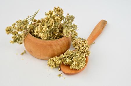 milfoil: Dry Milfoil flowers - Achillea Millefolium in a small wooden bowl with wooden teaspoon