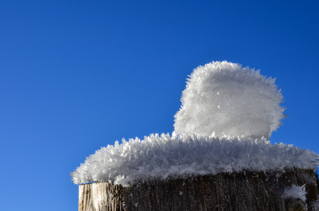 Winter detail of wooden fence - hoarfrost and snow on a wooden pole  photo