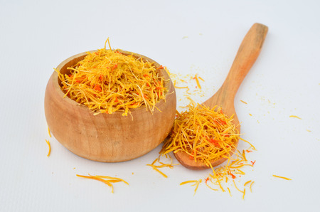 intense flavor: Dry Safroon - Crocus Sativus Tridaceae, in small wooden bowl with teaspoon  Stock Photo
