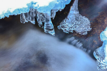 Detail of frozen brook -  icicles and milky stream