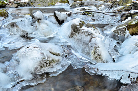 Detail of frozen brook - icy cascade, small waterfall, stones, icicles on branches and stones and milky stream photo