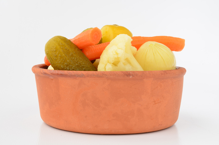 Mixed, pickled vegetables in rustic, clay bowl photo