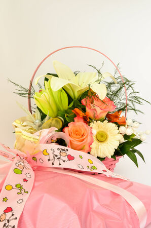 Flower arrangement in a pink wicker basket with a gift wrapped in pink paper in foreground, isolated on white background photo