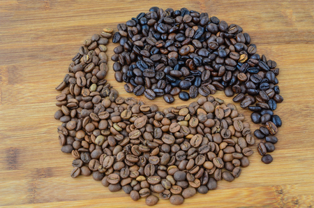 unroasted: Yin Yang shape made of well roasted and unroasted coffee beans on bamboo wooden surface