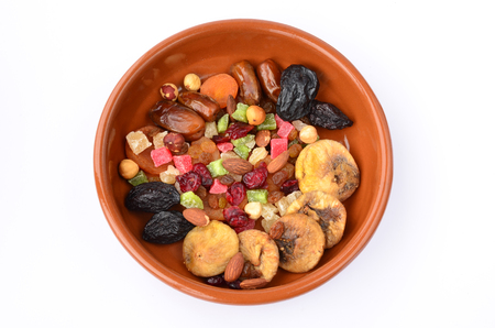 Different sorts of dried fruits in orange clay bowl isolated on white background, view from above photo