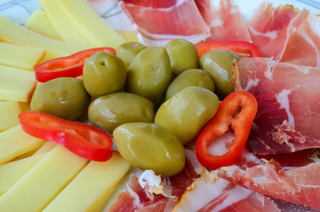 Green olives with sliced prosciutto, smoked sheep cheese and a few pieces of red, hot peppers photo