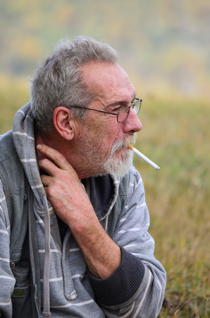 hombre fumando: Retrato de un anciano con barba gris y gafas, sentado en la hierba, el fumar cigarrillos y rascándose el cuello Foto de archivo