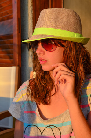 preteen girl: Preteen girl with hat and sunglasses in sunset light