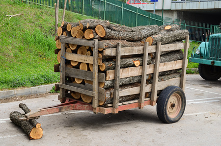 Small quantity of oak tree firewood in the tractor trailer, waiting on the marketplace for customer Stock Photo - 27717920