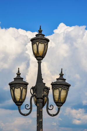 Detail of street lamp against blue sky and white clouds background photo