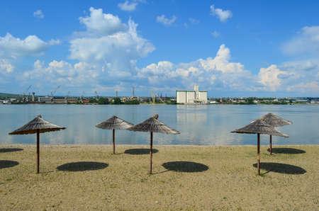Rivier strand aan de Donau en de industriële zone aan de andere kant van de rivier