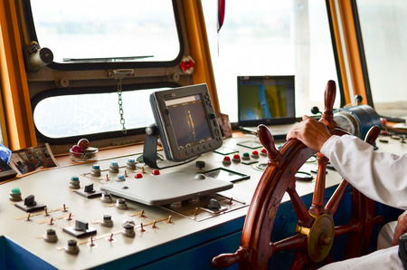 timon barco: Cierre la vista en cabinas del capit�n, equipo de navegaci�n y de la mano del capit�n en el tim�n durante el crucero Foto de archivo