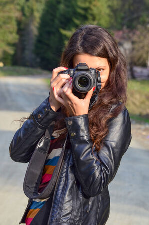 Young brunette girl wearing black leather jacket with DSLR camera, taking photo of nature photo
