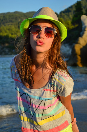 Preteen girl with hat and sunglasses in sunset light on a beach photo