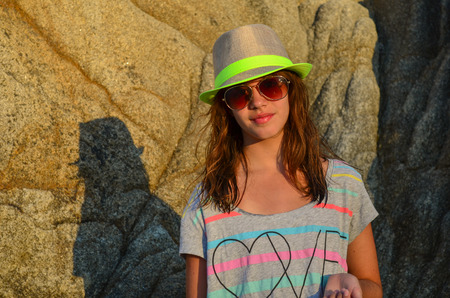 Preteen girl with hat and sunglasses in sunset light in front of big rock photo