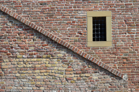 Brick wall with diagonal line and window with iron grid, constrained by yellow stone  photo