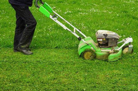 Mowing the grass, a worker maintains lawn using lawnmower Stock Photo