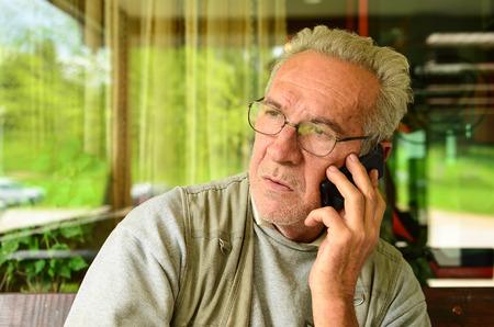 hombre preocupado: Acabamos de escuchar las malas noticias - hombre de edad usando el tel�fono m�vil