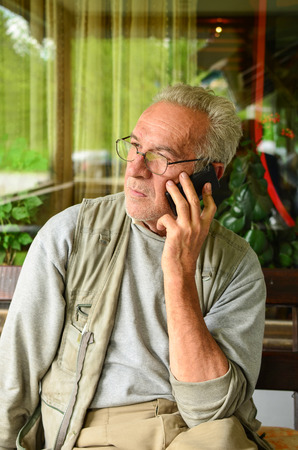 concerned: Aged man using cellphone, looking anxious after some bad news