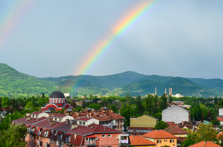 Double rainbow after summer storm, symbolically pointing the chirch photo