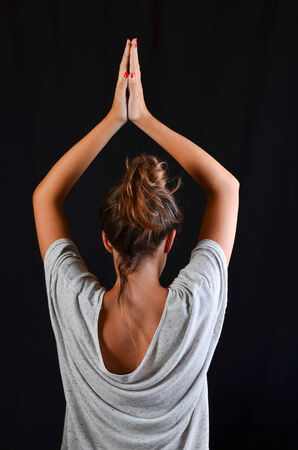 Teenage girl doing exercise in yoga pose, studio shot against black background photo