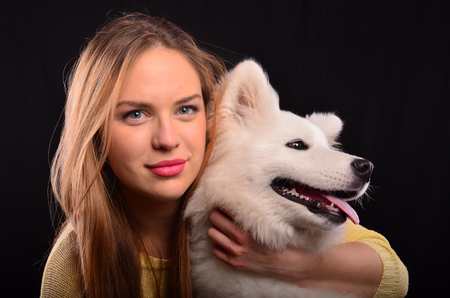 siberian samoyed: Portrait of beautiful blonde girl and young Samoyed dog with snow-white fur Stock Photo