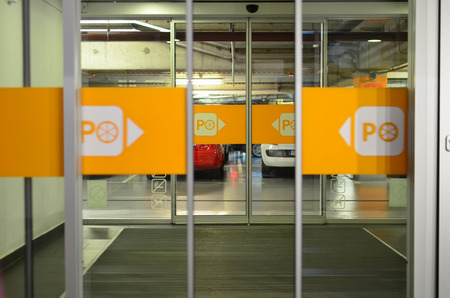 shopping centre: Garage entrance, opened glass door in a shopping centre with parking mark