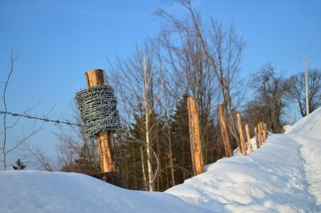 Reel of barbed wire on a wooden pale, part of half done barbed wire fence besides snowy footpath photo