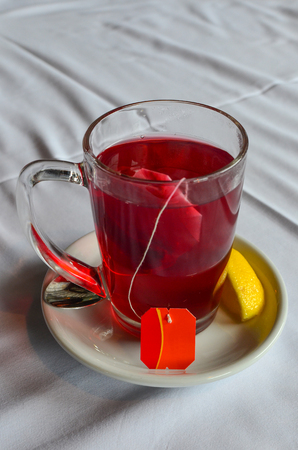 tea filter: Filter bag of hibiscus tea in a glass on white, ceramic saucer with slice of lemon Stock Photo