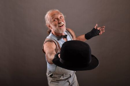 outworn: Old cheerful hobo posing with outworn, black hat, studio shot against gray background