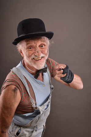 obscene: Obscene gesture of old homeless but cheerful tramp wearing jeans, black gloves and hat Stock Photo