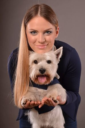 cute westie: Cute blonde girl playing with young Westie dog, studio shot, grey background