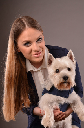 cute westie: Girl and West Highland Terrier wearing similar blue jackets, studio shot, grey background