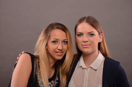 bright eyed: Friends, two young girls posing in studio after makeup completed Stock Photo