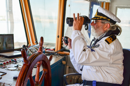 water wheel: Old experienced captain observes using binoculars by left hand and holding radio comunication equipment by right hand Stock Photo