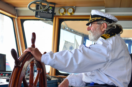 Ship navigation, experienced captain, old sea dog with grey hair and beard on his working place, ship navigation cabine Stockfoto