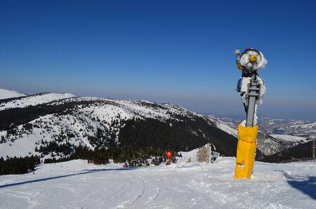 serbia landscape: Yellow snow gun on red, level six marked ski slope and mountain landscape, ski resort Kopaonik, Serbia