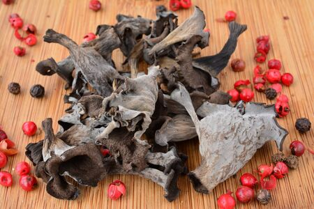 horn of plenty: Pile of dried Horn of plenty or Craterellus cornucopioides mushrooms with spicy red pepper on bamboo wooden chopping board over white background, top view