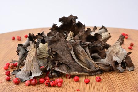 horn of plenty: Pile of dried Horn of plenty or Craterellus cornucopioides mushrooms with spicy red pepper on bamboo wooden chopping board over white background, side view