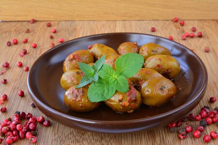 peppery: Peppery green olives in brown ceramic saucer, hot and spicy, decorated with green mint leaves and red pepper on wooden background Stock Photo