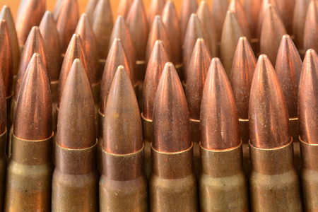 caliber: Lot of AK-47 Kalsnjikov rifle 7.62x39 caliber bullets in a row, close up view Stock Photo